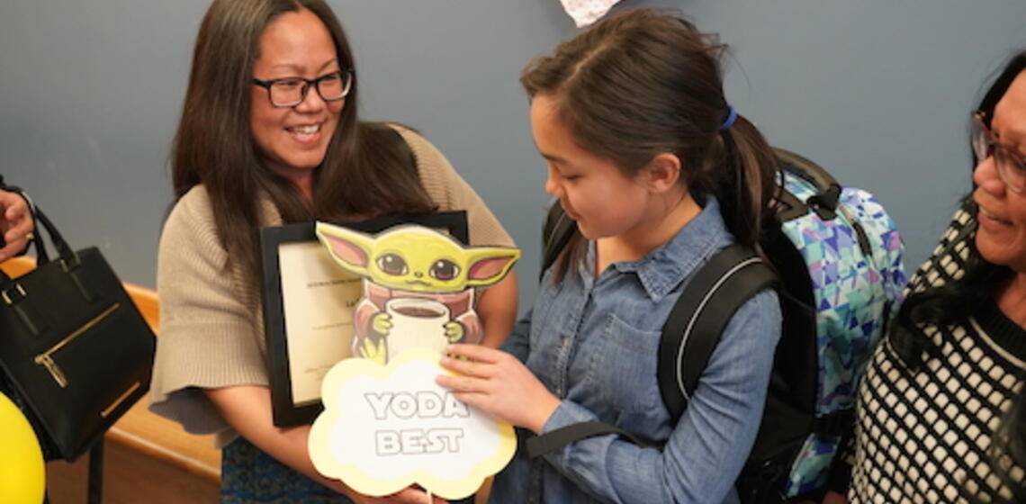 """An awards recipient accepting a graphic reading """"Yoda Best"""""""